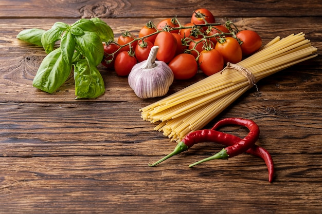 Italian food ingredients with raw pasta spaghetti on old rustic woodden table
