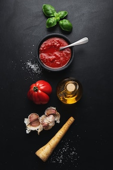 Italian food ingredients with vegetables and tomato sauce on dark table. top view.
