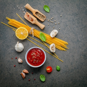 Italian food and menu concept spaghetti with ingredients on dark table .