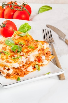 Italian food recipe. dinner with classic lasagna bolognese with bã©chamel sauce, parmesan cheese, basil and tomatoes, on white , coopy space