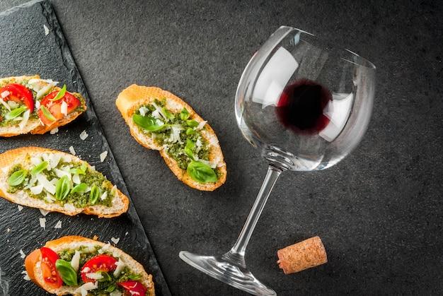イタリア料理。おやつ。前菜。ペストソース、パルメザンチーズ、トマト、新鮮なバジルのブルスケッタ。黒いテーブル、スレートボード。赤ワインのグラス。トップビューコピースペースセレクティブフォーカス