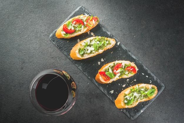 イタリア料理。おやつ。前菜。ペストソース、パルメザンチーズ、トマト、新鮮なバジルのブルスケッタ。黒いテーブル、スレートボード。赤ワインのグラス。トップビューcopyspaceセレクティブフォーカス