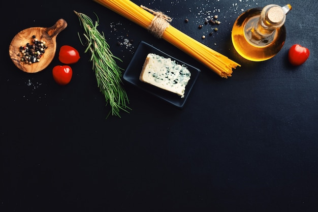 Italian food surface with vegetables, cheese and pasta on dark surface