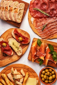 Italian food table with ham, cheese, olives.