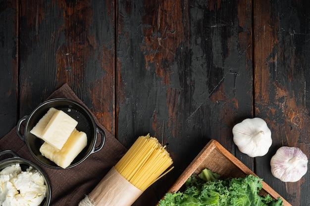 Итальянская еда. набор овощей, оливкового масла, зелени и макарон на старом темном деревянном столе