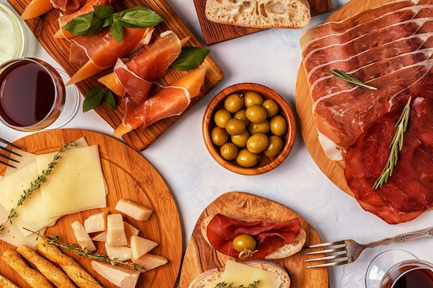 Italian food with ham, cheese, olives, bread and wine