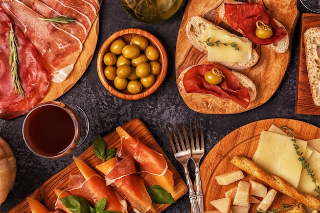 Italian food  with ham, cheese, olives, bread, wine.