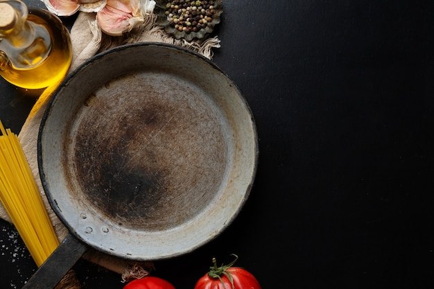 Итальянская еда с овощами спагетти и сковородой на темном столе. вид сверху.