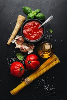 Italian food with spaghetti vegetables and tomato sauce on dark table. top view.