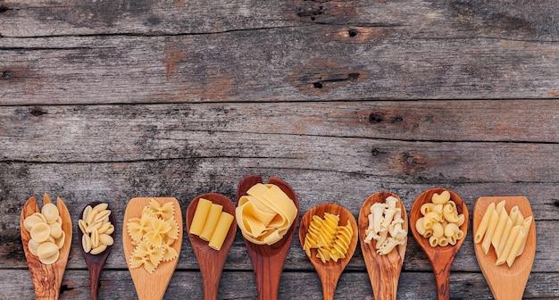 이탈리아 음식 컨셉과 메뉴 디자인. 다양한 종류의 파스타 팔꿈치 마카로니, 파팔레, 리가토니, 나무 숟가락에 있는 뇨코 사르도가 나무 배경에 설치되어 있습니다.