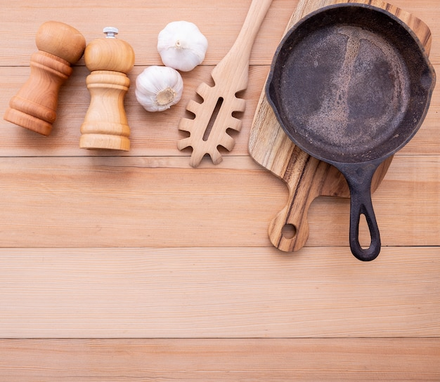 Italian foods concept and menu empty cast iron skillet on wooden table.