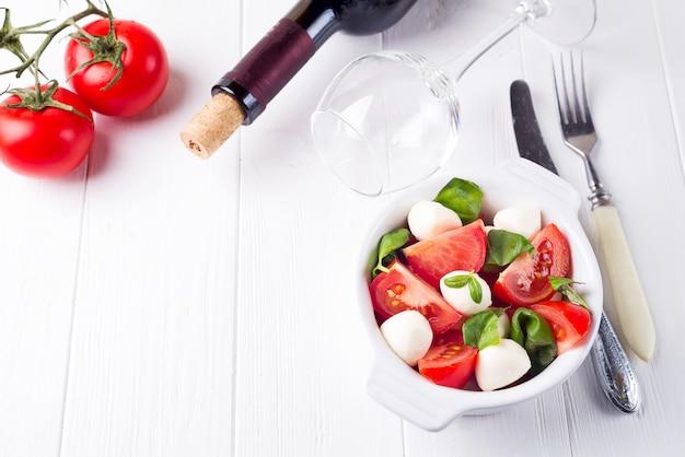 Italian fresh tomato caprese salad with ripe slice tomatoes and mini mozzarella cheese