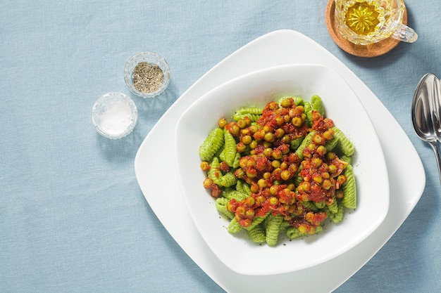 Italian fresh traditional sardinian pasta gnocchi with spinach and green pea tomato sauce.