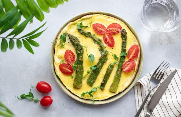 Итальянская фриттата со спаржей, помидорами и зеленью зеленого горошка здоровый завтрак
