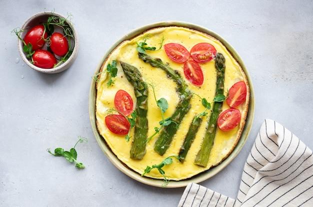 Итальянская фриттата со спаржей, помидорами и микрозеленью в керамической тарелке вкусная утренняя еда