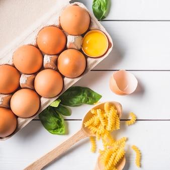 Italian fusilli pasta ingredients on white wooden plank