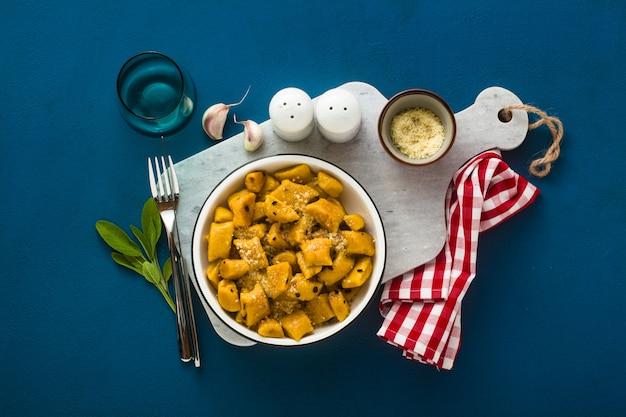 青色の背景にあるプレートのパルメザンチーズとカボチャからイタリアのニョッキ。伝統的な料理