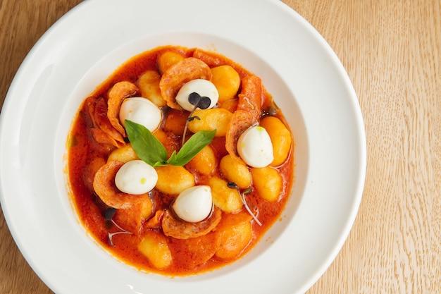 Italian gnocchi in tomato sauce with mozzarella, fresh basil and chorizo
