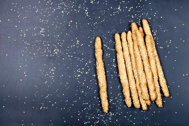 Italian grissini bread sticks with sesame seeds on black board. fresh italian snack.