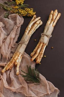 Итальянский гриссини или соленые хлебные палочки на коричневом фоне с цветами и бежевой тканью