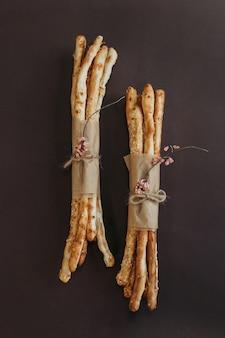 Итальянский гриссини или соленые хлебные палочки на коричневом фоне