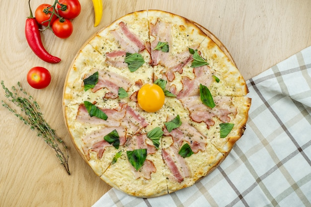 卵黄とベーコンの木製のテーブルでイタリアの自家製カルボナーラピザ。コピースペース平面図食品。フラットレイ