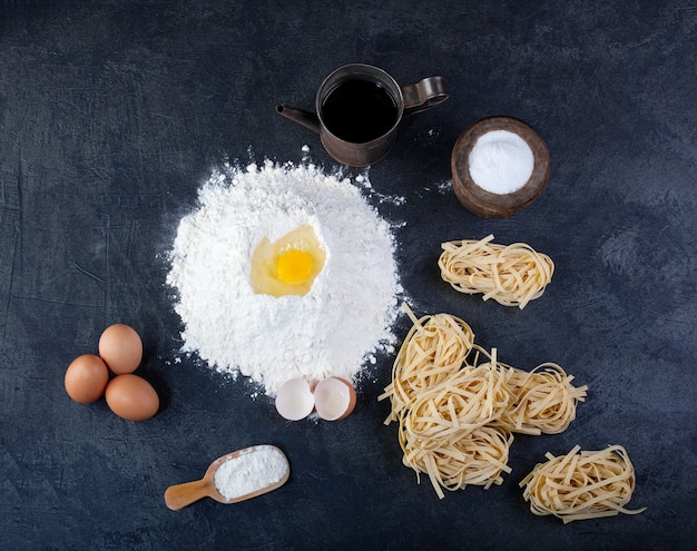 Italian homemade pasta called fettuccine, eggs and flour on dark table