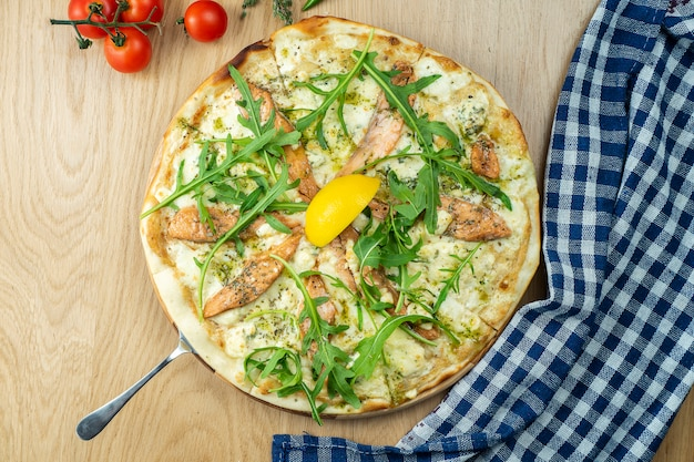 Italian, homemade pizza with salmonon dor blue cheese a wooden table.