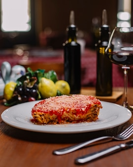 Italian lasagne garnished with tomato sauce and grated parmesan