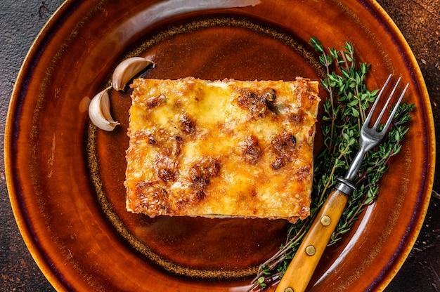 소박한 접시에 토마토 볼로네제 소스와 다진 쇠고기 고기를 곁들인 이탈리아 라자냐. 어두운 배경입니다. 평면도.