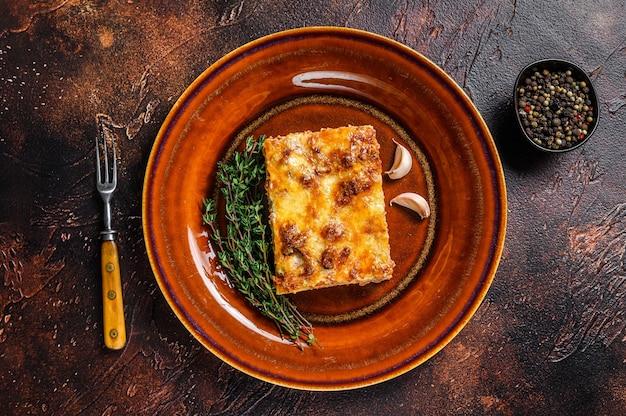 소박한 접시에 토마토 볼로냐 소스와 말하다 쇠고기 고기를 곁들인 이탈리아 라자냐