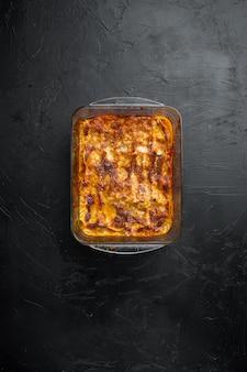 토마토 볼로 네즈 소스와 다진 쇠고기 고기 세트를 곁들인 이탈리아 라자냐, 베이킹 트레이, 검은 돌 위에