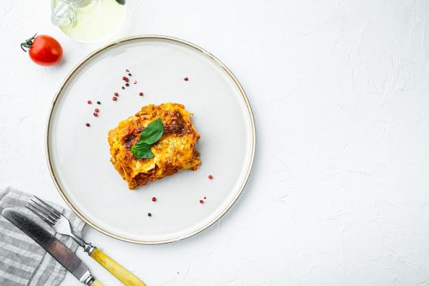 トマトボロネーゼソースと牛挽肉のイタリアンラザニアを白い石のテーブルトップビューのプレートにセットし、コピースペースで平らに置きます