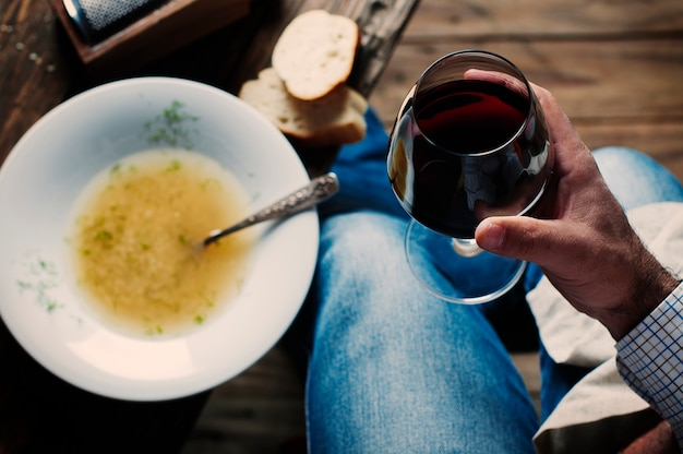 Italian man holding traditional soup with pasta minestra and wine