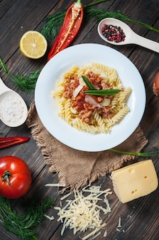 Italian meat sauce pasta and fresh delicious ingredients for cooking on rustic background.
