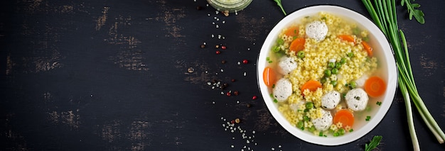 Итальянский фрикадельки суп и stelline глютен макароны в миску на черном столе.