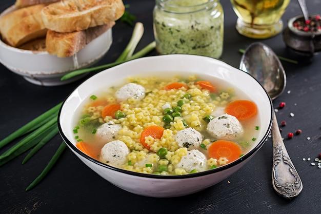 イタリアのミートボールスープと黒いテーブルのボウルにステリングルテンフリーパスタ。