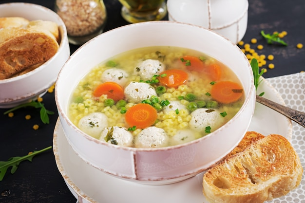 イタリアのミートボールスープと黒いテーブルの上のボウルにステリーネパスタ。栄養スープ。ベビーメニュー。おいしい食べ物。