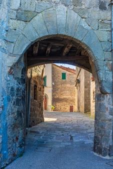 Детали итальянской средневековой деревни, историческая каменная арка, древние ворота, архитектура каменных зданий старого города. санта-фьора, тоскана, италия.