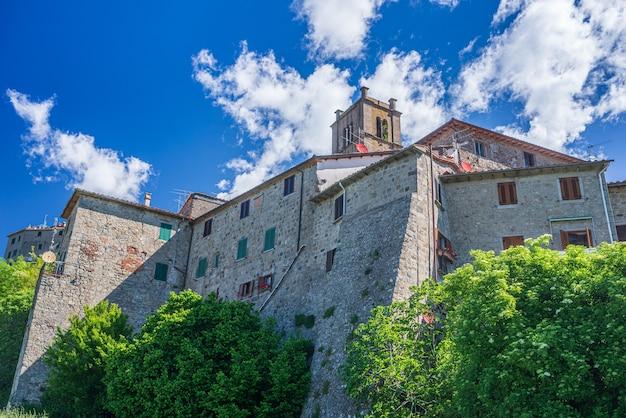 Детали итальянской средневековой деревни, историческая каменная церковь и аббатство, архитектура каменных зданий старого города. санта-фьора, тоскана, италия.