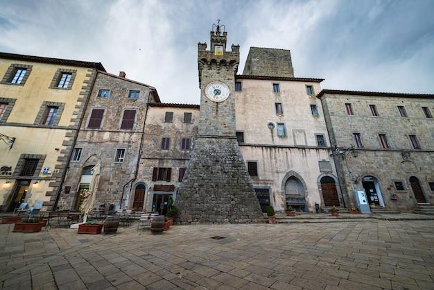 Детали итальянской средневековой деревни, историческая каменная площадь и древняя башня с часами, архитектура каменных зданий старого города. санта-фьора, тоскана, италия.