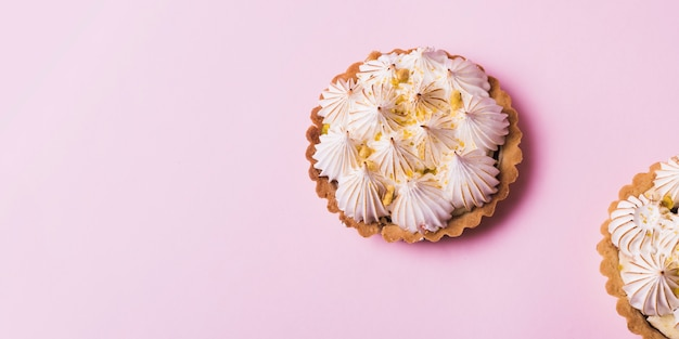 Italian meringue on tartlets against light pink backdrop