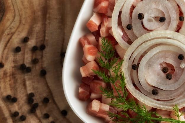 イタリアのパンチェッタ、ベーコンキューブ、さいの目に切ったハム、カットポーク、スライスした玉ねぎ、木製のテーブルの上の正方形の白いプレートにコショウ