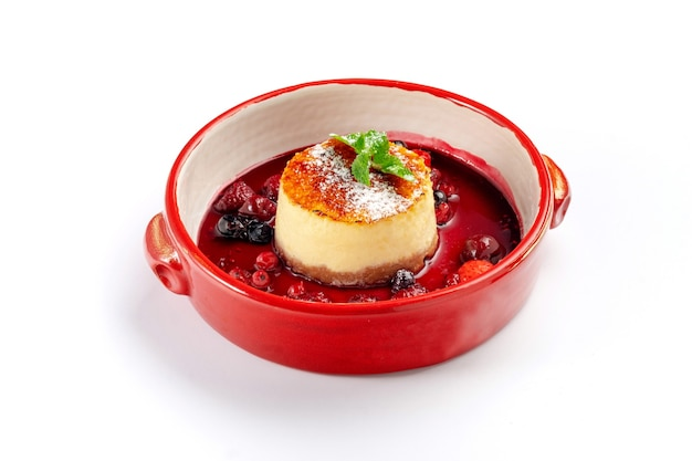 Italian panna cotta dessert with strawberries and wild berries in a bowl isolated on white
