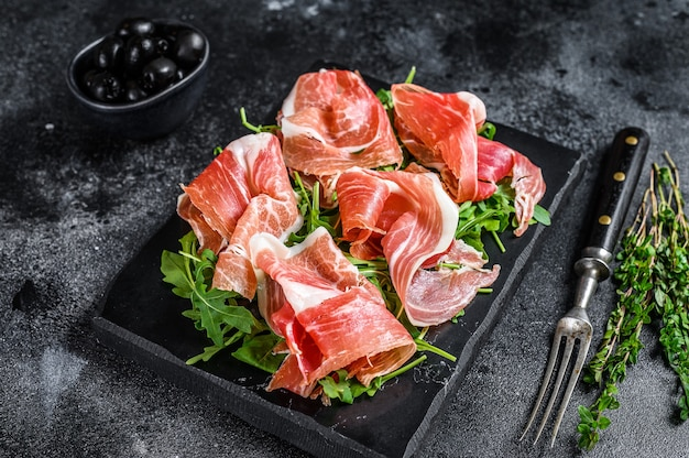 Italian parma prosciutto crudo dried ham on a marble board. black table. top view.