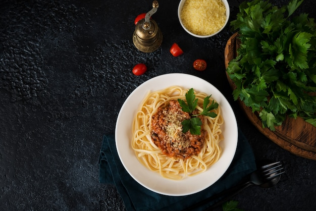 Italian pasta bolognese with greens on a black background, copy  space