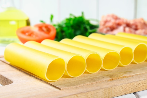 Italian pasta cannelloni. raw tube for stuffing stuffing surrounded by ingredients for cooking