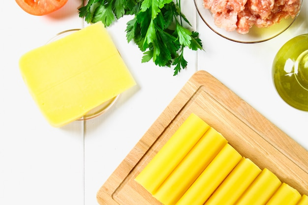 Italian pasta cannelloni. raw tube for stuffing stuffing surrounded by ingredients