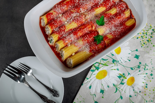 Italian pasta cannelloni with meat and tomato sauce and cheese on table