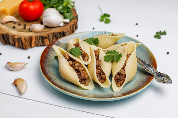 Italian pasta conchiglioni rigati stuffed with meat.